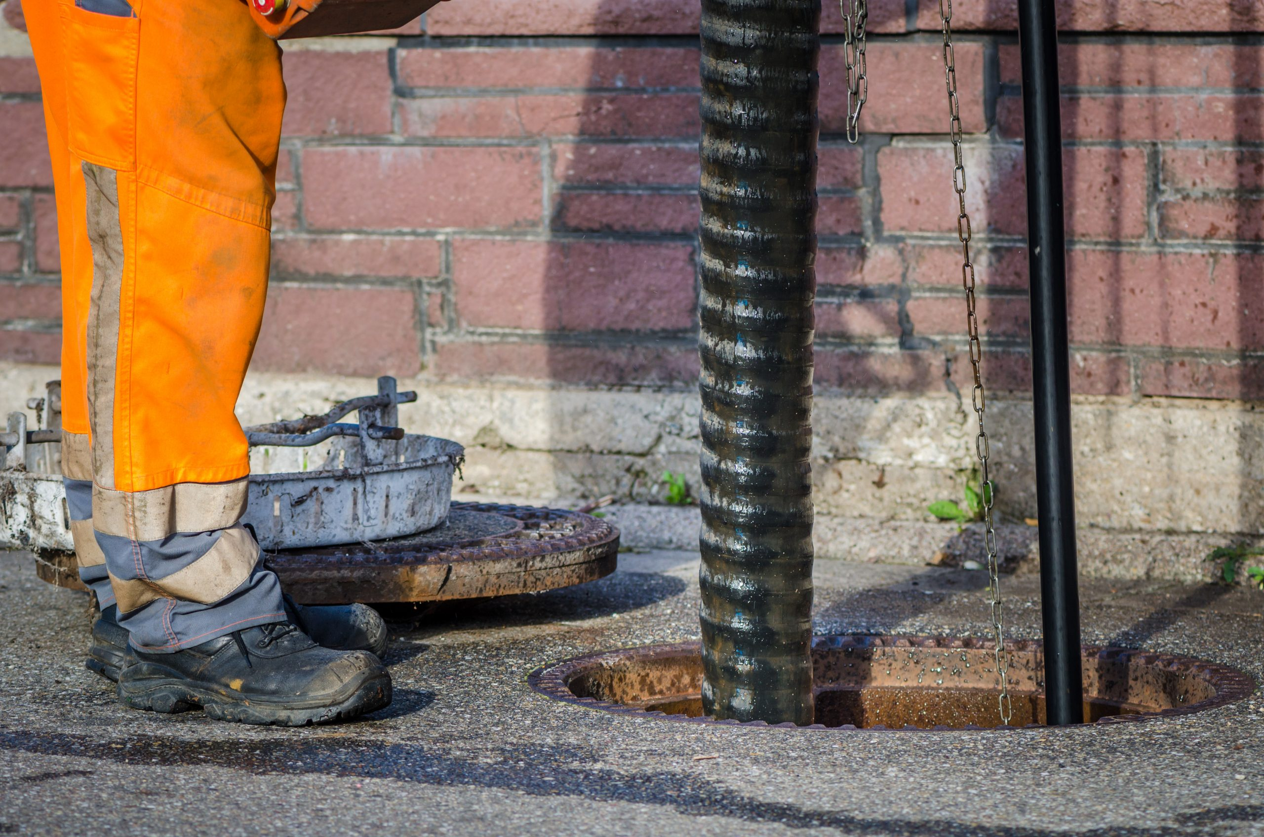sewerage worker on street cleaning pipe